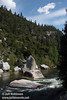 The dark waters of the Merced River flowing by white granite boulders in the forested canyon against a blue sky with white clouds. Seen at a turnout (the 2nd we stopped at) by the Merced River on El Portal Road (highway 140) (5/15/2010, Yosemite NP)<br /> EF-S17-85mm f/4-5.6 IS USM @ 24mm f11 1/250s ISO160