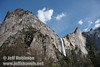 Bridalveil Fall, Leaning Tower (right), and the leading edge of Cathedral Rocks (left) with foreground trees against blue sky dappled with clouds. Seen at the turnout on Southside Drive north of Bridalveil Fall (5/15/2010, Yosemite NP)<br /> EF-S17-85mm f/4-5.6 IS USM @ 17mm f9 1/200s ISO100