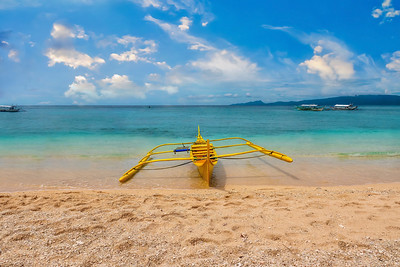 A small outrigger boat on a beach in the Philippines.