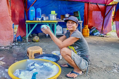 A Filipino woman living under plastic tarpaulins, with a dirt floor and only basic necessities, because she can't afford to pay rent.