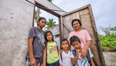 A woman and four of her children standing in front of their small, roofless, concrete  house after the husband suddenly died before he could replace the storm-damaged roof.