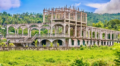 A failed tourism project resulting in an abandoned hotel in a former rice paddy after the owner ran out of cash.