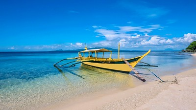 A traditional Filipino wooden outrigger boat (banca) anchored on a gorgeous tropical beach.