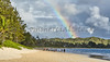 People and dogs on Kailua Beach with rainbow after sunrise rains