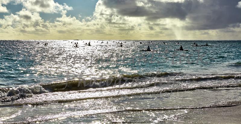 People kayak over ocean shore surf at sunrise in Hawaii