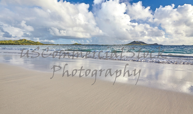 smooth sandy beach and sky shore reflections in Hawaii
