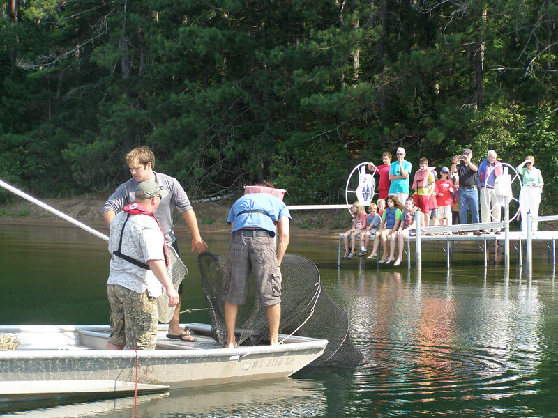 As visitors watch from the dock, Zach Lawson, Greg Sass (of the Wisconsin DNR) and summer student, Yuri ..., pull the Fyke net up into their boat.