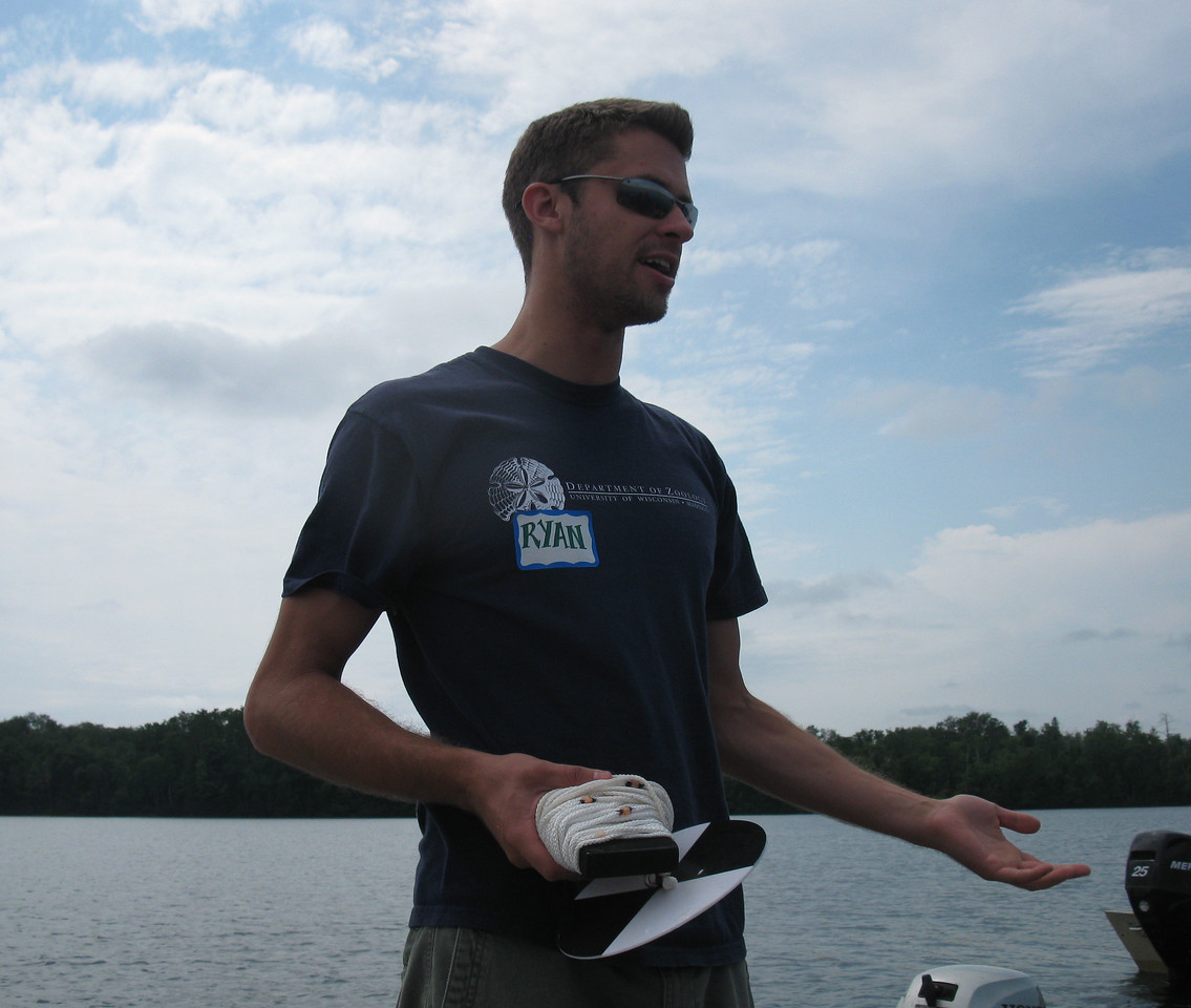 UW graduate student Ryan Batt explains how a secchi disk is used to determine water clarity in a lake.