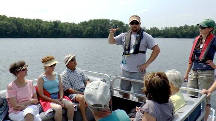 Researcher Noah Lottig and undergraduate student Ellen Albright talk about the Long-Term Ecological Research program with visitors on a pontoon ride