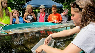 Graduate student Adrienne Gemberling shares her research on rusty crayfish and banded mystery snails with younger visitors