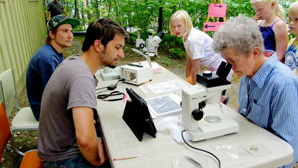 Weevil crew members Jim Miazga and Nick Winter point out stages of the aquatic insect's life cycle under a microscope
