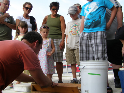 Research technician, Eric Brown, demonstrates how fish are weighed and measured as a crowd looks on.