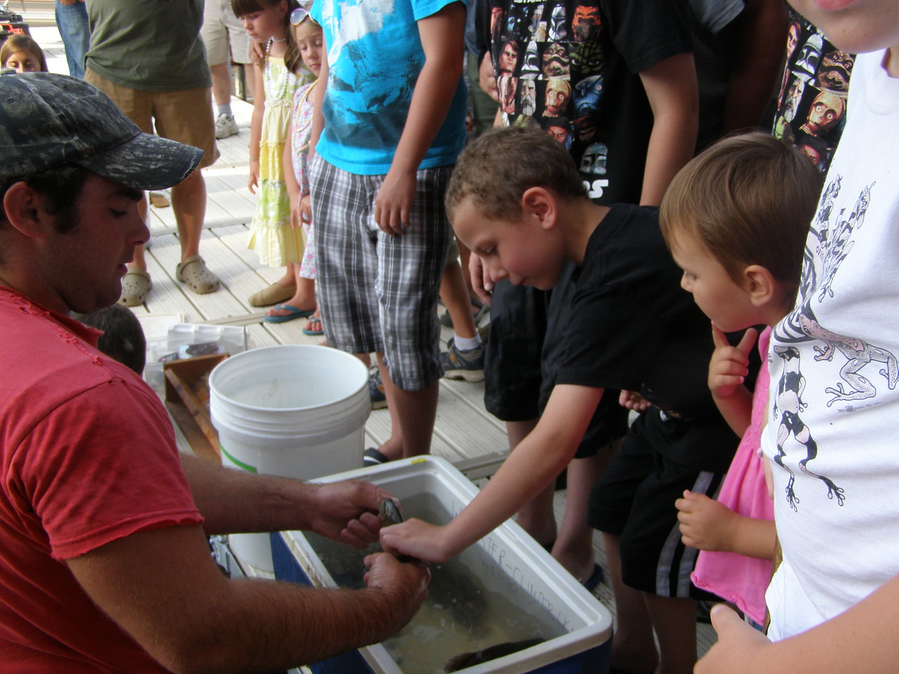Kids get a chance to feel the fish before they're released back into the lake.