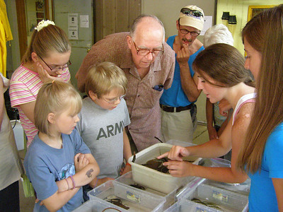 Students Amanda Brown and Lindsey Bruckerhoff explain how to spot a rusty crayfish to a visiting family.