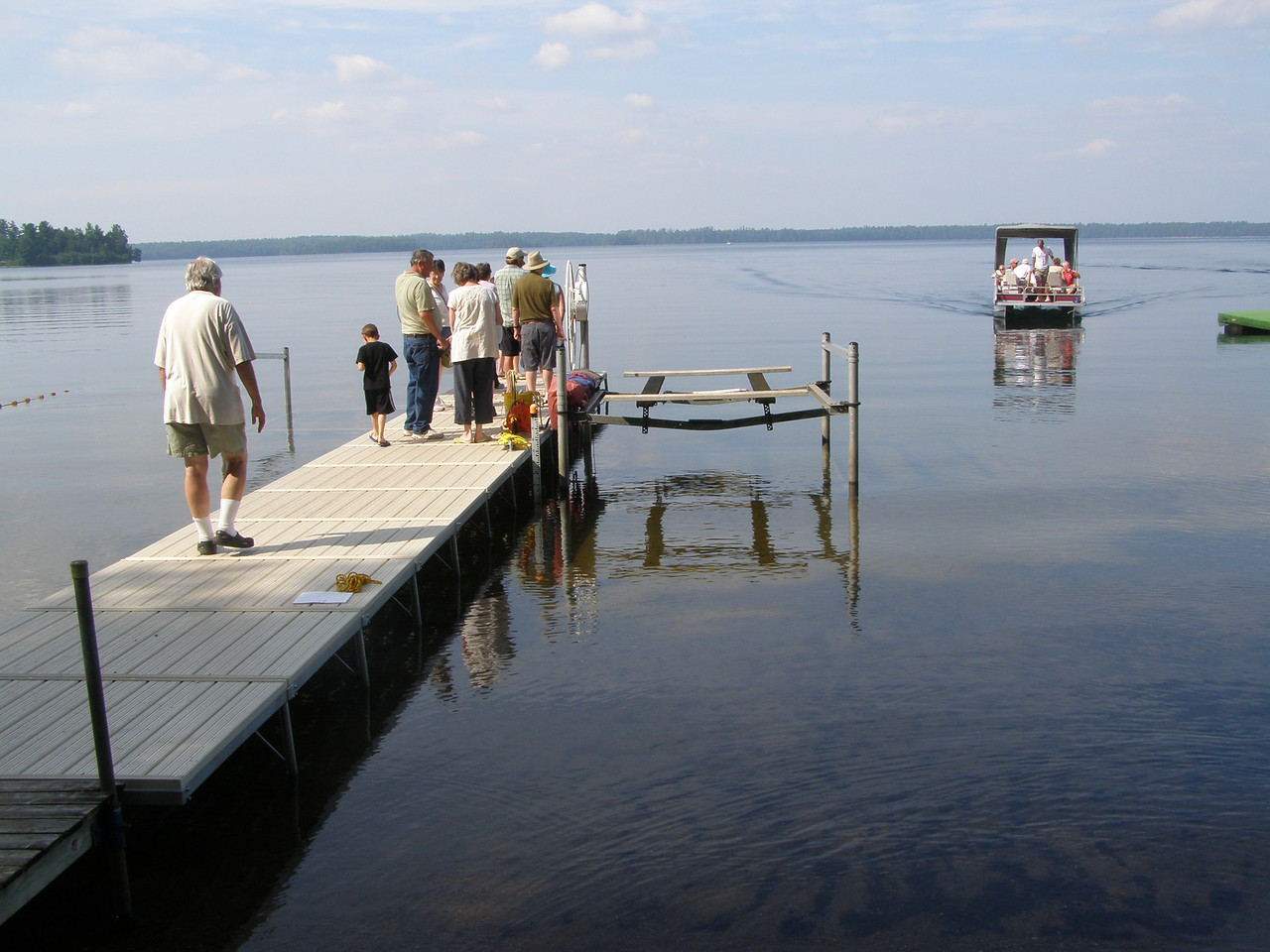 """As a boat returns from it's """"limno"""" expedition on the lake, visitors line up for the next departure."""