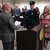 MARK ROBARGE - MROBARGE@TROYRECORD.COM<br /> Troy Mayor Patrick Madden, left, gives the oath of office to newly promoted Troy Fire Department Lt. Andrew Dolan, standing with his mother, Toni, during a Monday morning ceremony in City Hall.