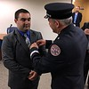 MARK ROBARGE -- MROBARGE@TROYRECORD.COM<br /> Troy Fire Department recruit Robert Jones has his badge pinned on by his uncle, department Capt. Paul Denio, during a ceremony Monday morning in City Hall.