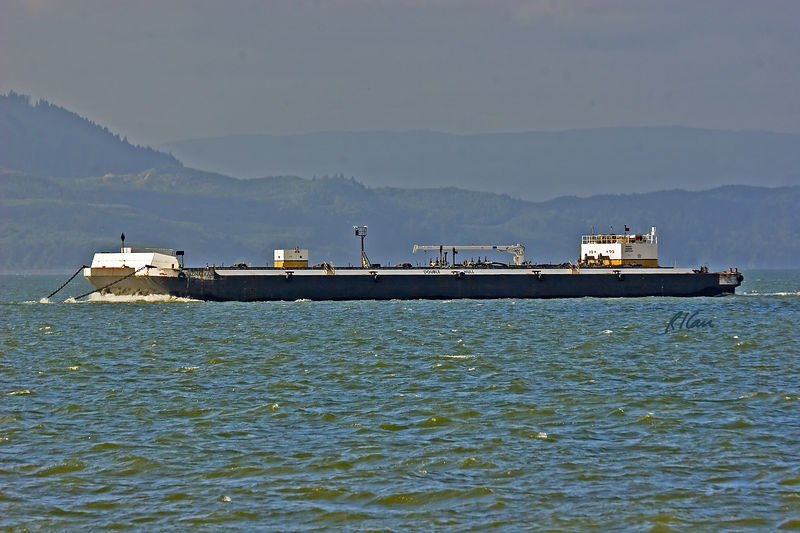 Marine transportation and construction: Unmanned tank bunker barge Shauna Kay being towed by a tug boat on lower Columbia River. The double hull barge is 82.7 meters long and carries 40,988 barrels of oil. Astoria, Oregon 2005.<br /> The tug boat James T. Quigg or Portland, Oregon towing a barge by cable on the lower Columbia River. 2005