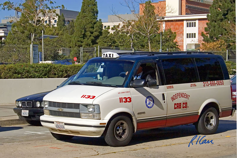 Taxi cab: Independent Cab Co., Chevrolet van taxi cab driving street. Los Angeles, CA 2004.