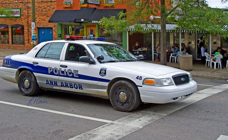 Police cruiser/car: Ann Arbor Police Ford cruiser/automobile traveling North on Ashley Street downtown in front of Fleetwood Diner. Ann Arbor, Michigan 2005.