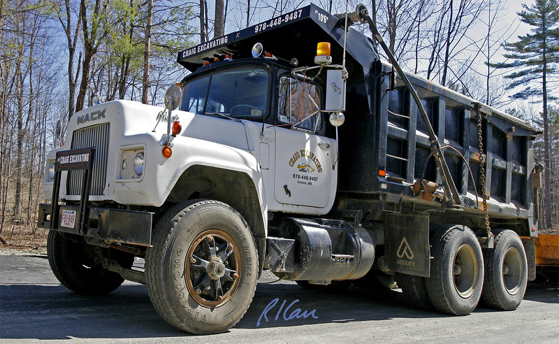 Earthmoving construction: Mack dump truck, pulling a low-boy equipment trailer. Pepperrel, Massachusetts, 2005.