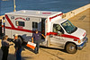 Ambulance/emergency medical vehicle: Ambulance answers emergency medical call from ship on Columbia River while in locks at dam. Emergency medical technician carries emergency medical kit onboard to assist injured member of ship's crew. City of Pasco Fire Department, Pasco, Washington, 2005