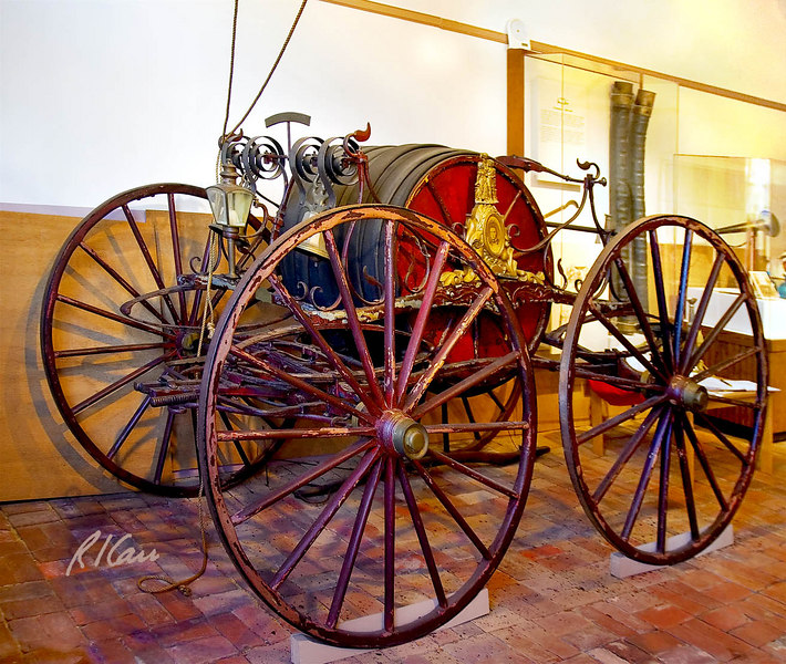 """Hand pulled four wheel fire hose carriage built by R. F. Prettyman, long-time Friendship Fire Company Member and carriage maker, in 1858. It features portraits of two Friendship members, with two clasping hands symbolizing """"Friendship."""" Friendship Firehouse Museum, Alexandria, Virginia, November 2006."""