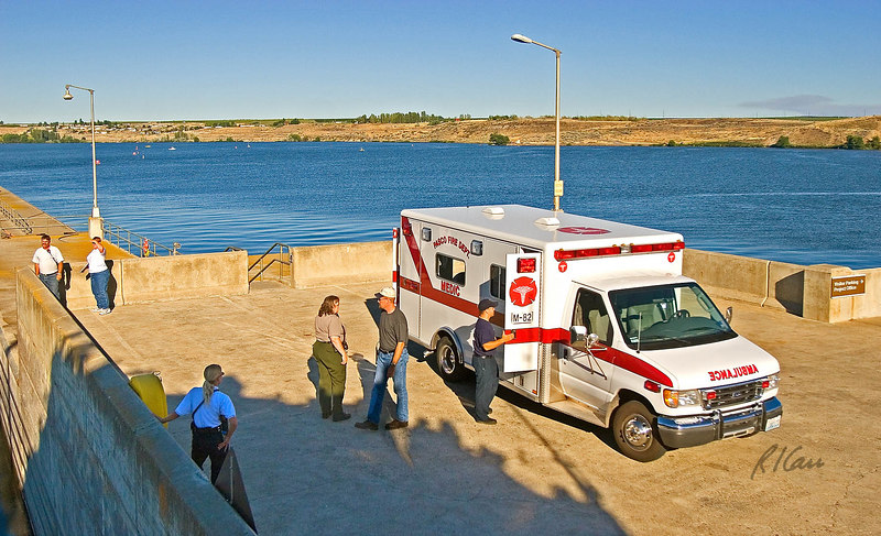Ambulance/emergency medical vehicle: Ambulance answers emergency medical call from ship on Columbia River while in locks at dam. Emergency medical technician is picking up emergency medical kit from ambulance side compartment to take onboard to assist injured member of ship's crew. City of Pasco Fire Department, Pasco, Washington, 2005