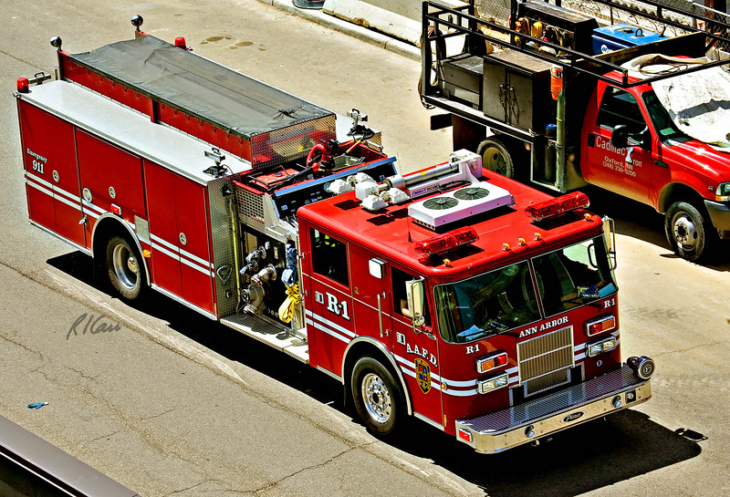 Fire truck, engine, apparatus: Ann Arbor Fire Department 1982 E-One heavy rescue truck R1 turns from Huron to Ashley heading north with siren/horn blasting to answer call. Ann Arbor, Michigan, May, 2007