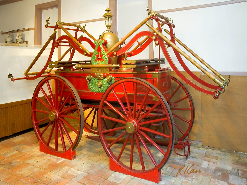 Suction pump and hand pumper manufactured by Rodgers of Baltimore in 1851 and owned by the Friendship Fire Company. It is pumped by several people at either end standing on the ground, facing the machine and by several other people standing on the wood planks on top of the pumper facing outward. The groups at the two ends alternate pushing down and pulling up. Friendship Firehouse Museum, Alexandria, Virginia, November 2006.