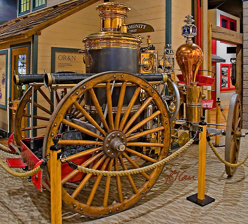 Antique fire engine: 1879 Amoskeag Steam Fire Engine: The Jackson Number 1. Purchased by The Dalles, Oregon from the Manchester Locomotive Works of New Hampshire in 1879, it pumped water at 550 gallons per minute. The bed for the fire in the steamer was laid in advance so it could be started when the engine cleared the doors of the station. The steamer was continuously hooked up to the steam boiler of The Dalles City hall, keeping the water in the chamber pre-heated. It took about 10 minutes with this head start for a good head of steam to build up, about as long as it took to get to the fire. The steam in the chamber then forced the pistons of the pump to go up and down, causing the water to flow. The Jackson Number 1 was retired from service by 1915, when motorized engines arrived. Columbia Gorge Discovery Center, The Dalles, Oregon, 2005.
