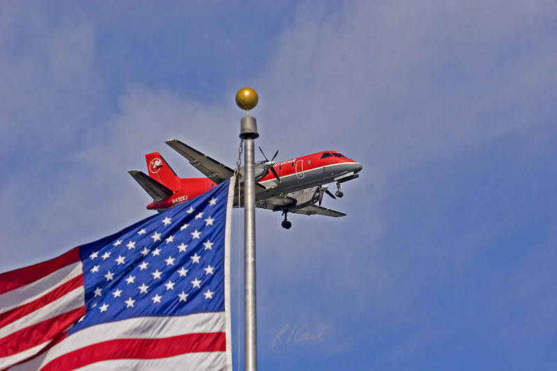 Air transportation, airplane: View from Nomads Air Terminal of Northwest Airlines Airlink turboprop plane approaching Detroit Metro Airport above and beyond Nomads' American Flag. Taken upon return from Lewis and Clark trip, July 23, 2005.