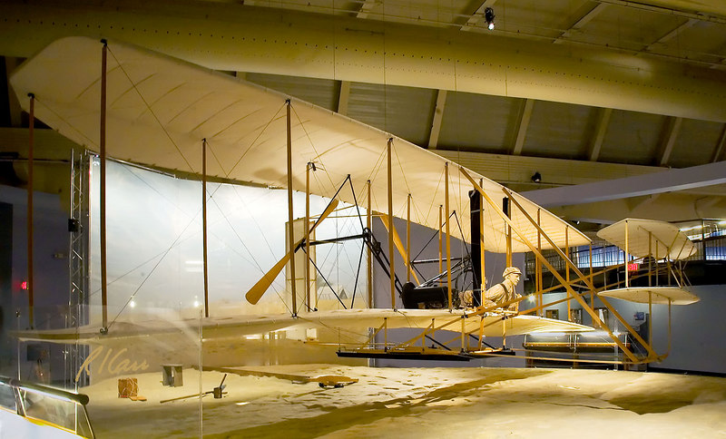 """'This Wright Flyer is the world's most accurate reproduction of the original 1903 Flyer. Just weeks before the Centennial of Flight celebration in December 2003, this Flyer made several successful flights at the Wright Brothers National Memorial in Kill Devil Hills, North Carolina. Trained pilots attempted to fly this reproduction on Dec. 17--exactly 100 years after the Wright brothers' original first flight. Unfortunately, rain and low wind speed prevented the Flyer from getting up in the air on that day.<br /> <br /> 'The Experimental Aircraft Association (EAA) commissioned The Wright Experience of Warrenton, Virginia, to build this authentic reproduction in celebration of 100 years of flight. As a sponsor of """"EAA's Countdown to Kitty Hawk,"""" Ford Motor Company generously donated this Flyer to the collection of The Henry Ford.' Henry Ford Museum, Dearborn, Michigan. Photo in August, 2006."""