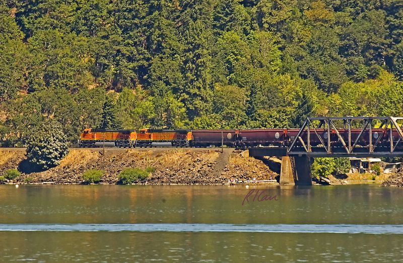 Train/Rail transportation: Two Burlington Northern Santa Fe Railway diesel locomotives pull a freight train up the rails beside the Columbia River separating Oregon from Washinton. July 2005.<br /> The tug boat James T. Quigg or Portland, Oregon towing a barge by cable on the lower Columbia River. 2005