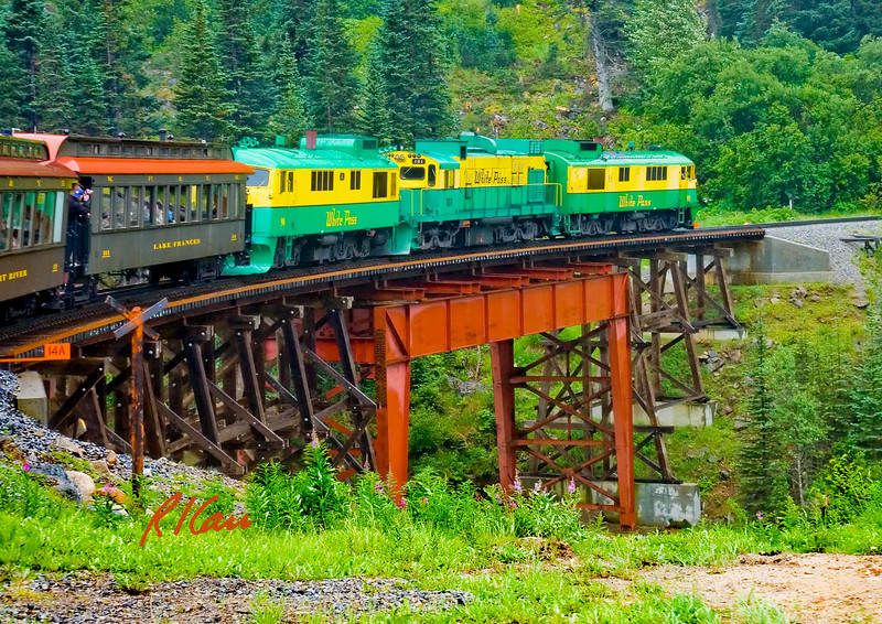 Diesel locomotives and passenger cars of White Pass and Yukon Route railroad cross trestle bridge headed down to Skagway from White Pass on a misty day. Alaska, August, 2007.
