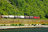 Freight train of tank cars travels along stone embankment on north bank of Rhine River. Germany, July, 2006.