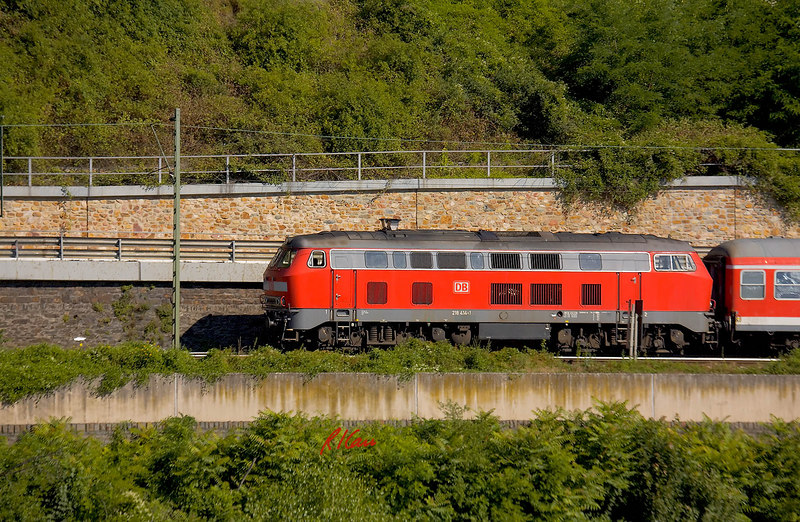 Diesel locomotive pulls passenger train along bank of Rhine River, Germany. July, 2006