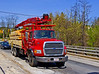 Construction services: Ford L9000 flatbed truck with IMT 13034 3-4 story knuckle boom material loading/ unloading crane. Truck carries full load of dimension lumber and plywood across the Merrimack River for delivery to a construction site. Tyngsborough, Massachusetts, 2005