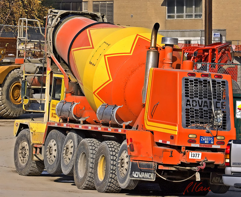 Concrete construction: Concrete ready-mix truck loaded with concrete to cast in place. Front of truck is to left, and concrete is chuted out from top, left, of the rotating drum. Primary chute is just forward of driver's front window. Additional sections of chute are attached to top of long truck rear fender, to be fitted together as needed to transport concrete further. Truck is traveling on its front-steering axle and 2 of its 5 rear axles. Cardiovascular Center, University of Michigan Hospital, Ann Arbor, 2004.