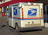 Postal service vehicle/van: USPS postal van doing mail delivery/pickup at Meijer. Ann Arbor, MI 2004.