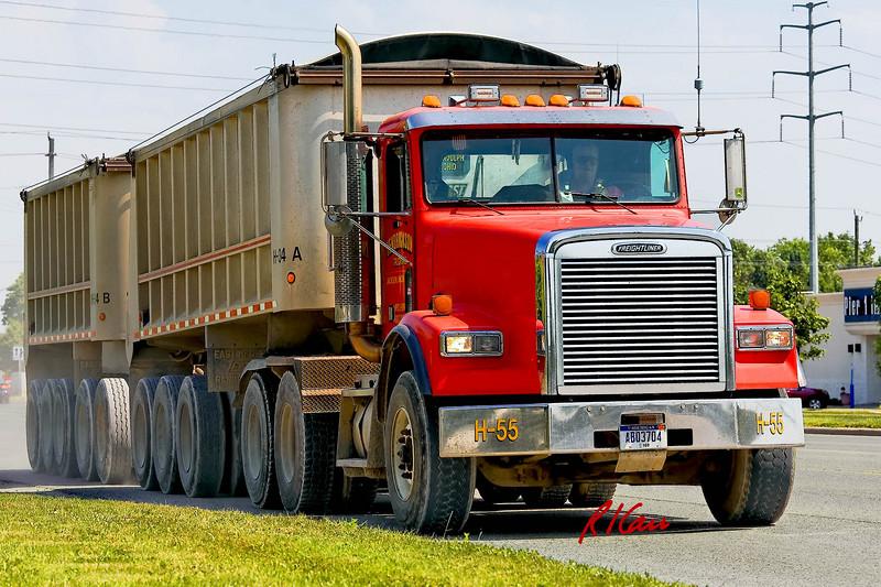 Freightliner semi-tractor pulls semi-trailer and tandem trailer filled with soil. Carpenter Road, Ann Arbor, Michigan June2007.