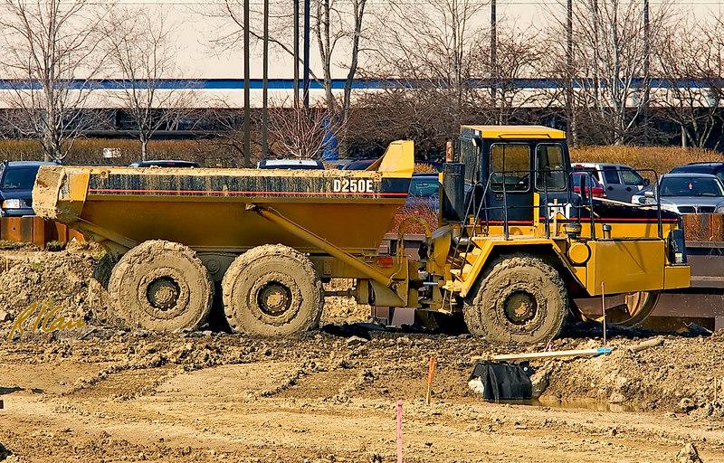 Construction equipment: Caterpillar D250E 25 ton, articulated, rear dump, rough terrain, off road hauler. Plymouth Green Crossings, Ann Arbor, Michigan, March 2007.
