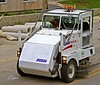 Construction maintenance: Three wheel Elgin Pelican Series P mechanical street debris broom sweeper. Street debris is swept onto a conveyor that transports it to a debris hopper. Ann Arbor, 2003.