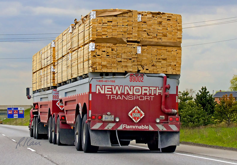 Wood construction, construction materials: Manitoulin lumber tanker is solution to a particular backhaul problem, carrying a load for only one way of a two way haul. The lumber tanker transports bulk fuel (80% of a standard tanker) to lumber processing mills and hauls out a full load of finished lumber, 2x6's in this case. Ontario, Canada, 2005.