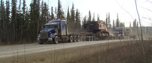 A pair of Carlile Kenworth T800's labor to get a heavy load up a steep grade, with the rear tractor, pulling a much lighter load, using its push bumper to give some assistance.
