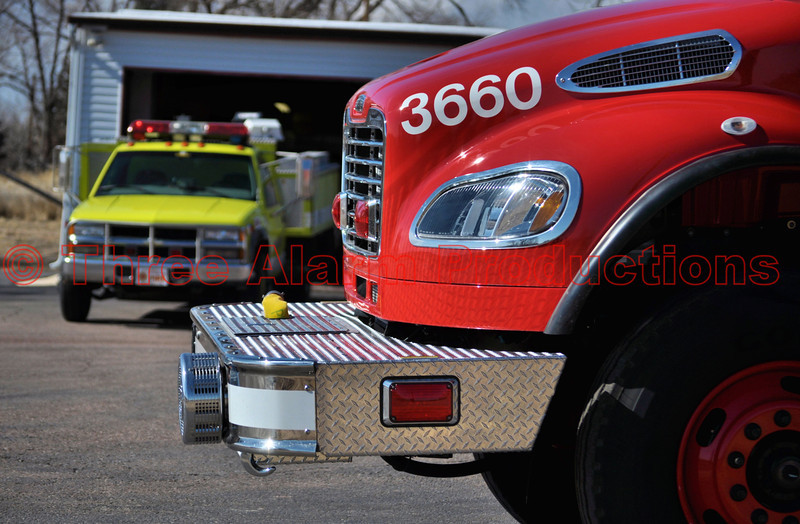 Peyton Fire Protection District just recently received delivery of a 2013 Freightliner Fire Pumper/Tender, combination apparatus. Peyton Fire is located in a community, in rural eastern El Paso County, Colorado, USA. This new truck has a large capacity water tank of 3000 gallons. This dual pump truck has a Hale 500 gallon per minute pump that allows for pump and roll capabilities, like for a grass fire. The truck has sprayer nozzles under each corner of the front bumper. The 3 crosslay compartments located above the pump panel hold two setups of 200 foot, 1 & 3/4 inch hose, and one run of 200 foot, 2 & 1/2 inch fire hose. Two port-a-tanks, one on each side, have a holding capacity of 2000 gallons each. The apparatus is equipped with supply line: 600 feet of 3 inch line for a forward lay and 600 feet of 3 inch line set up for a reverse lay. This rig is outfitted with ten Goodyear G291 Tires.