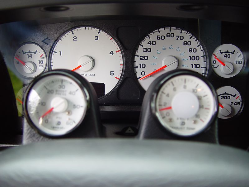 Mounted on top of the steering column, on the left is a Boost gauge, it monitors the amount of boost the Turbo-Charger is producing at any given time.  On the right is a Pyrometer, it registers the exhaust temperature before it enters the Turbo-Charger.  The probe for the Pyro is mounted pre-turbo and at a place in the exhaust manifold where it will measure the hottest exhaust gases.