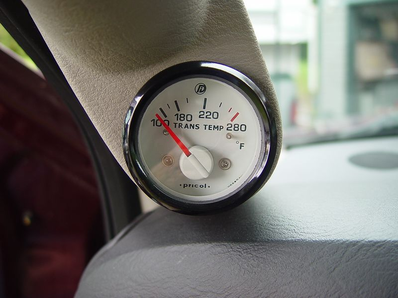 "Mounted on the ""A"" pillar, is a Auto transmission fluid temperature gauge.  The sending unit is mounted in the cooling line that goes from the transmission to the cooler, this gives a reading that represents the hottest fluid in the system."