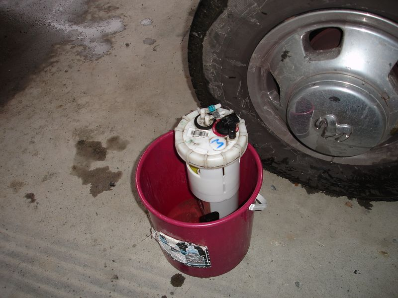 The fuel pump and sending unit is stored in a bucket while the work is done.