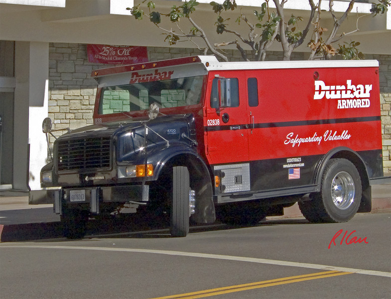 Armored car: Dunbar armored car, built on International truck base, pulls away from curb after picking up money from store. Los Angeles, CA 2004.